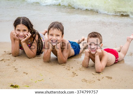 Three smiling kids on the beach lying down on the sand near water - stock photo