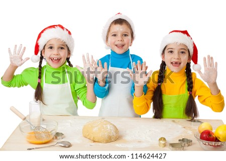 Three smiling kids with Christmas cooking and hands up sign, isolated on white - stock photo
