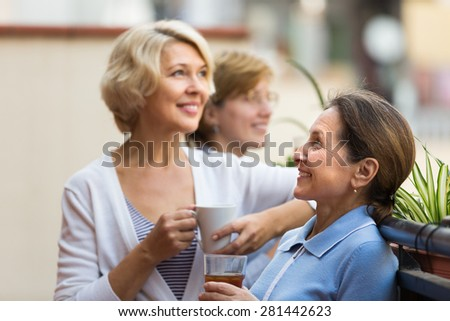 Three smiling mature women drinking tea with cookies at balcony. Focus on brunette