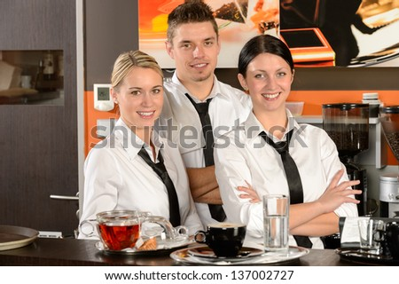 Three smiling server posing in uniform in cafe - stock photo