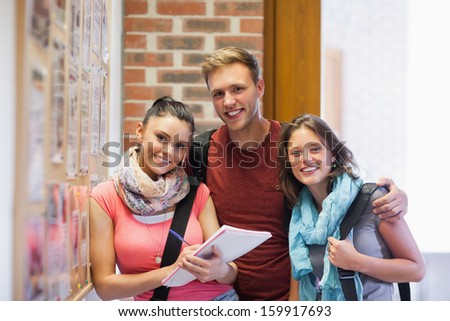 Three smiling students standing next to notice board in school - stock photo
