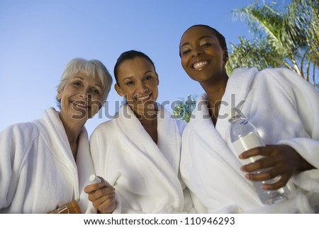 Three smiling women in bathrobe - stock photo