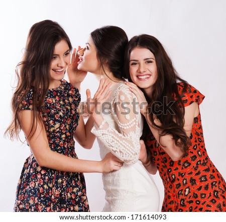 Three smiling women whispering gossip - stock photo