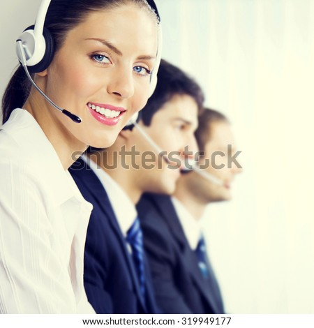 Three smiling young customer support phone operators at workplace, customer service concept - stock photo