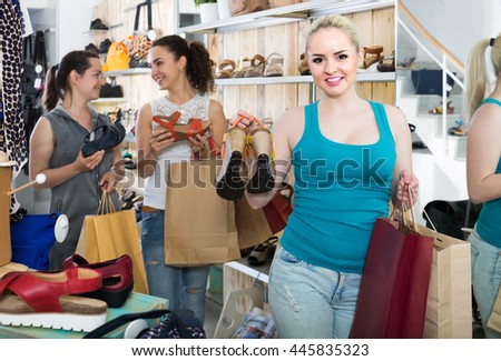 three smiling young girls spanish holding a paper shopping bags in the boutique - stock photo