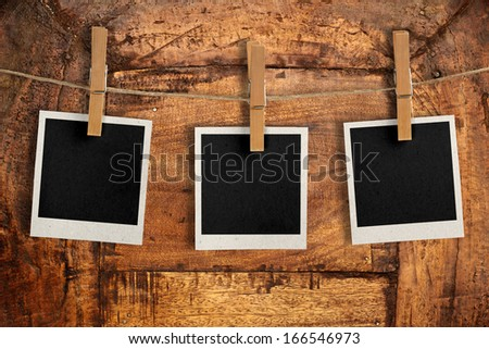 three snapshots hanging from a rope over an antique wooden board - stock photo