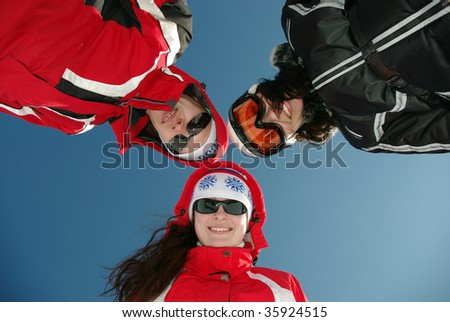 Three snowboarders smiling. - stock photo