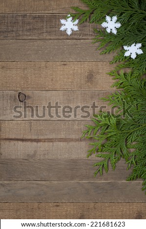 Three Snowflake Ornaments with Tree Greens on side of Used Rustic Wood Board Background with room or space for copy, text, words.  Vertical vintage, simple design - stock photo