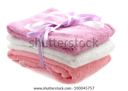 Three soft towels on a pile isolated over white - stock photo