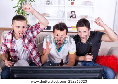 Three sports fans are watching game on TV at home. - stock photo