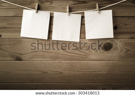 Three squares of blank paper, pegged to a string washing line, with wood plank fence in the background.  Low saturation and vignette gives a retro or vintage feel. - stock photo