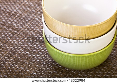 Three Stacked Colorful Bowls On Placemat - stock photo