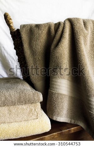 Three stacked terry cloth towels next to one towel draped over a wicker basket. Against a white backdrop with room for text. - stock photo