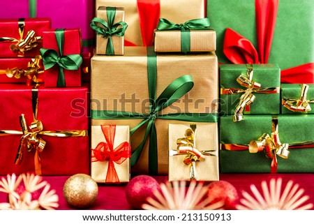 Three stacks of plain Christmas presents assorted by color. Red, gold and green. Blurred baubles and stars in foreground. Focus set on the green bow around the big golden box. Narrow depth of field. - stock photo