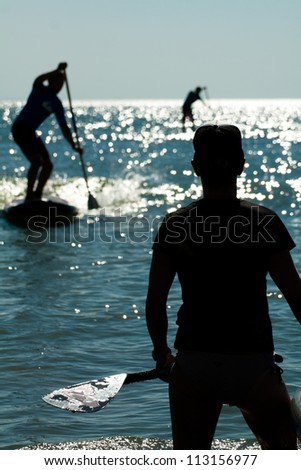 Three stand up paddlers shadows on the water - stock photo