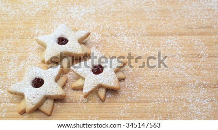 Three star-shaped cookies on a wooden table covered in flour. - stock photo