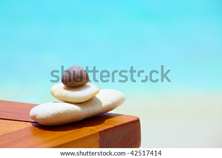 Three stones are on a beach table - stock photo