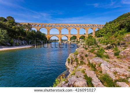 Three-storied aqueduct of Pont du Gard - the highest in Europe. The bridge was built at the time of Roman Empire on river Gardon. Provence, spring sunny day - stock photo