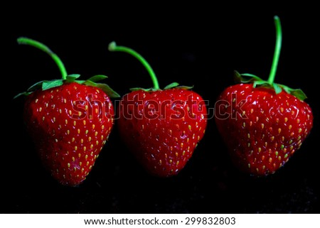 Three strawberries isolated on black background, shallow focus - stock photo