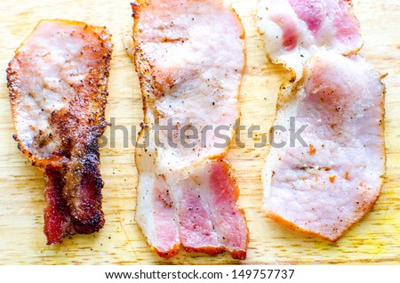 Three strips of cooked Canadian bacon - stock photo