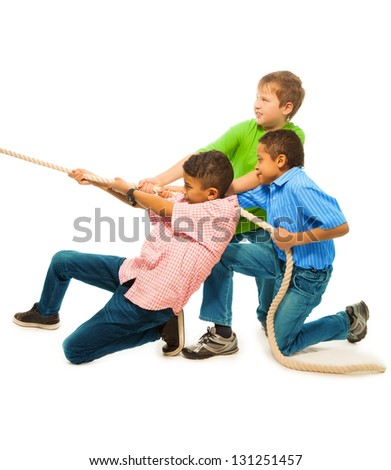 Three strong boys pulling the rope with strength standing isolated on white - stock photo