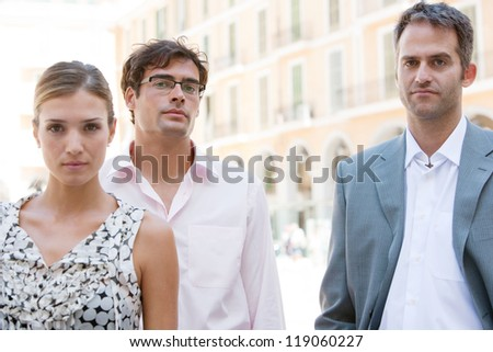 Three strong business people standing together next to a classic office building in the city on a sunny day. - stock photo