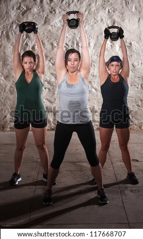 Three strong women lifting weights during boot camp workout - stock photo