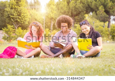 three students are studying sitting at the park - people, lifestyle and nature concept - stock photo