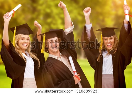 Three students in graduate robe raising their arms against trees and meadow - stock photo