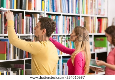 Three students looking for books and standing in a row in a library. - stock photo