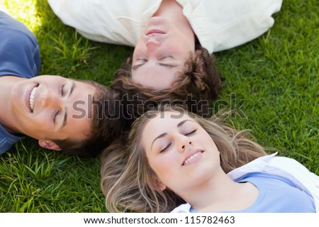 Three students resting together in the grass - stock photo