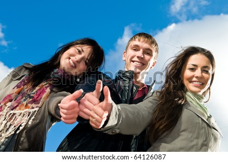 Three students standing over blue sky with thumbs up. Lower point of view - stock photo