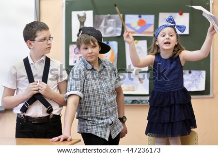 three students: two boys and one girl act out scene in class performance at drawing lesson - stock photo
