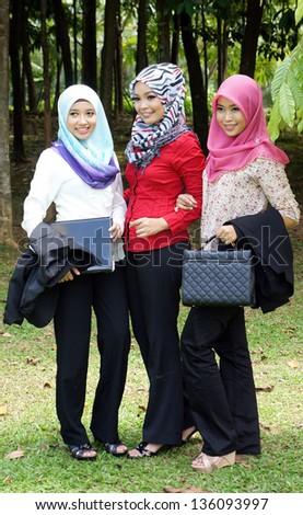 three stylish Muslim woman held a laptop and handbag - stock photo