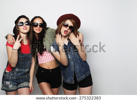 Three stylish sexy hipster girls best friends.Standing together and having fun.  Over gray background. - stock photo