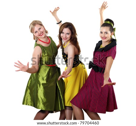 three stylish young woman in bright colour dresses - stock photo