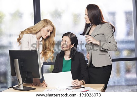 Three successful businesswomen working together as a team in the office - stock photo