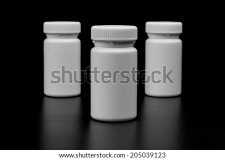 Three supplements, medications or vitamin bottles on black background - stock photo
