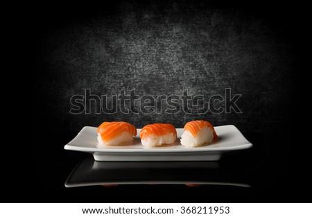 Three sushi on black - stock photo