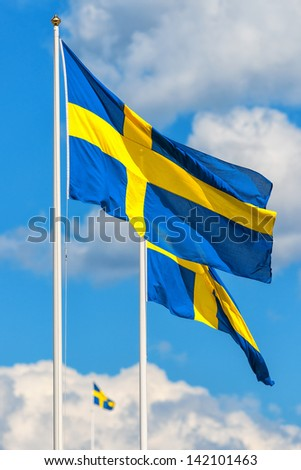 Three Swedish flags with the flag in front in focus on a typical summer sky in Sweden - stock photo