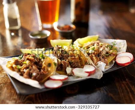 three tacos with beer on wooden table top served with limes, radish slices and beer,  shot with selective focus - stock photo