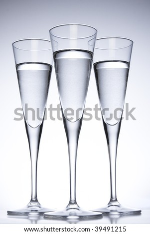 Three tall glasses filled with clear liquid - stock photo