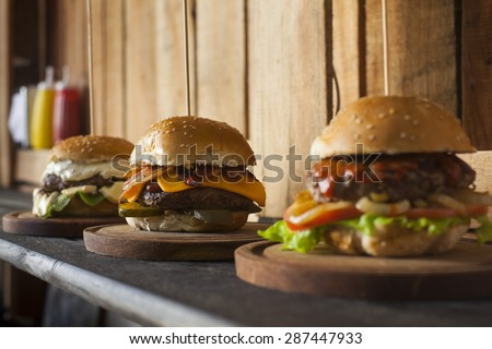 Three tasty different hamburgers on a wooden table. Bacon, pickles, and cheese. - stock photo