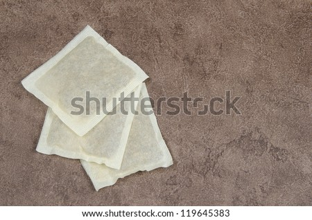 Three tea bags, green, herbal and black, on a brown counter top. - stock photo