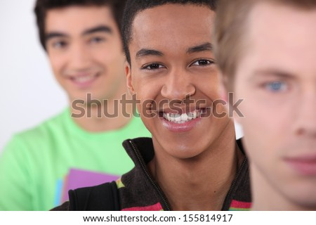 Three teenage age friends standing together - stock photo