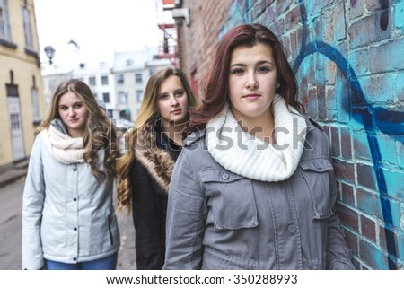 Three teenage girl friends have fun in city outdoors - stock photo