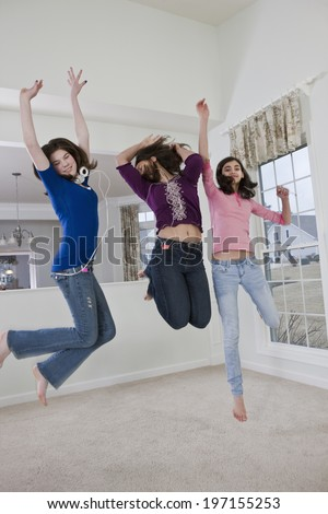 Three teenage girlfriends leaping and dancing to music at home in a carpeted living room - stock photo