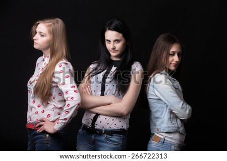 Three teenage girlfriends looking away from each other, unhappy and angry because of disagreement or argument - stock photo