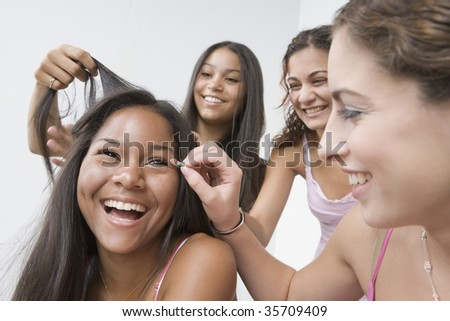 Three teenage girls helping their friend to get dressed - stock photo