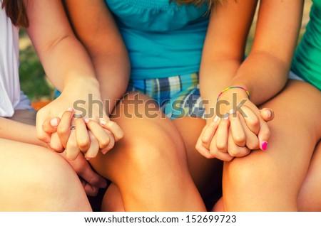Three teenage girls holding hands outdoor. - stock photo